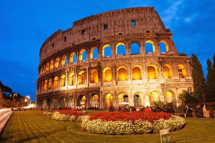 Beautiful view of Colosseum at sunset with flowerbed in foregrou