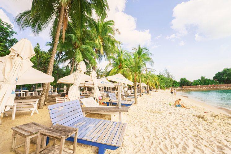 Tourists in Siloso Beach at Sentosa island resort in Singapore